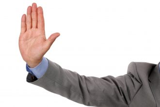 Businessman holds up his hand as a stop gesture